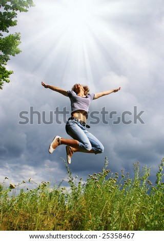 Happy young woman jumps. Sky as background