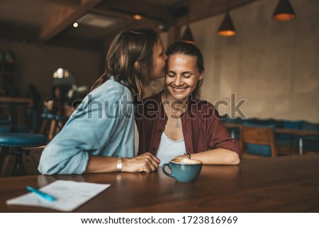 Happy young woman kissing her girlfriend, sitting in a cafe. Happy lesbian couple in love. Foto d'archivio ©
