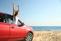 Happy young woman leaning out of car window on beach, space for text. Summer trip