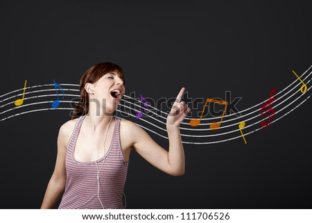 Happy young woman listen music and dancing, with musical notes in the background