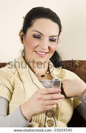 Happy young woman listening and enjoying music on mp3 player