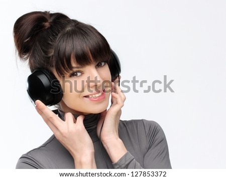 Happy young woman listening to music with a headphone.