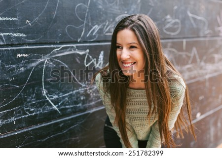 Happy young woman looking at camera. / Young beautiful woman standing in front a blackboard wall.