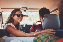 Happy young woman looking back with man driving car. Couple in a car going on roadtrip.