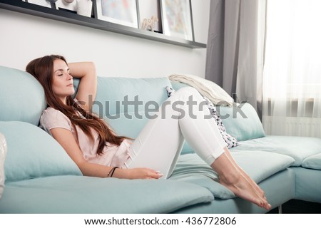 Happy young woman lying on couch and relaxing at home, casual style indoor shoot