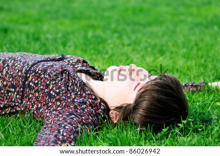 Happy young woman lying on green grass