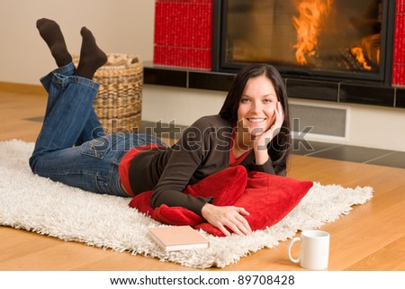 Happy young woman lying on rug by fireplace home living