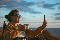 Happy young woman making video call with smartphone, sharing data on social media, holding iron mug cup with coffee, sitting in touristic chair on cliff in front of sea on sunset. Technology concept