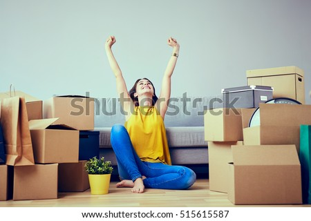 Happy young woman moving to new home - having fun #515615587