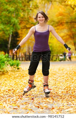 happy young woman on roller skates in the autumn park