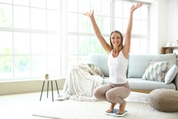 Happy young woman on scales at home. Weight loss concept
