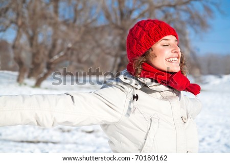 Happy young woman on the snow sunny day against blue sky