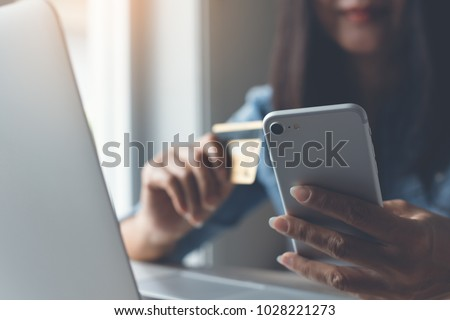 Happy young woman online shopping by credit card payment on mobile smart phone and laptop computer, internet banking, mobile banking, e commerce, e business, financial technology Fintech concept. #1028221273