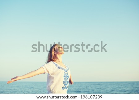 happy young woman open her arms to the sky and sea and enjoying life