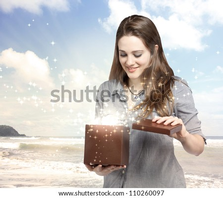 Happy Young Woman Opening a Gift Box