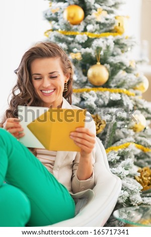 Happy young woman opening christmas letter in front of christmas tree