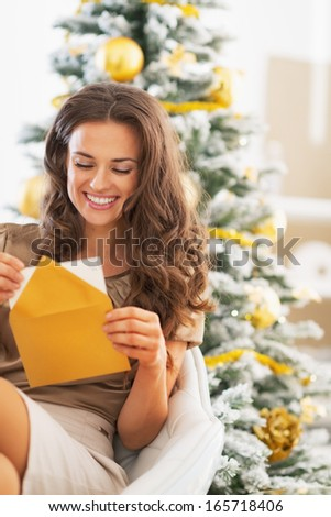 Happy young woman opening christmas letter near christmas tree