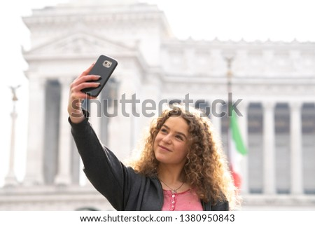 Happy young woman or tourist taking self portraits with her smartphone camera