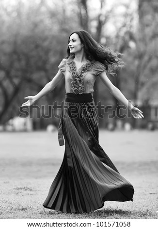 happy young woman outdoors in the field,dancing under the rain,black and white