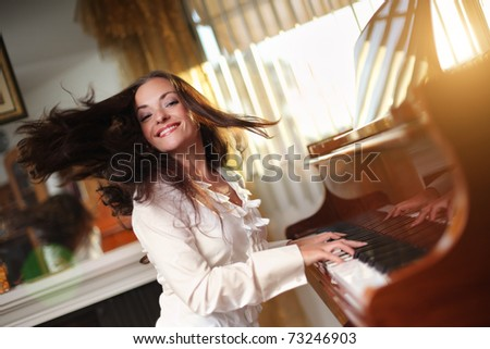 Happy young woman playing piano indoors. Closeup, shallow DOF. - stock photo
