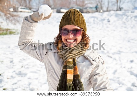 Happy young woman playing snowball fight on the snow sunny day