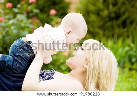Happy young woman playing with baby boy in spring flowery garden. Nature blurred background