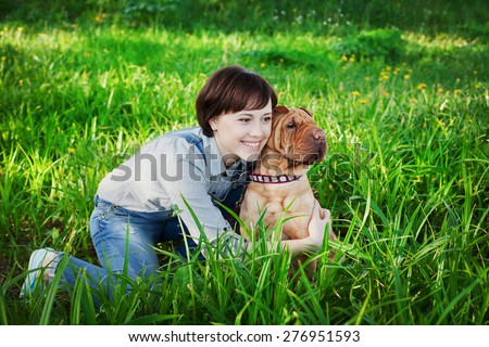 happy young woman playing with dog Shar Pei in the fresh green grass, true friends forever, people concept
