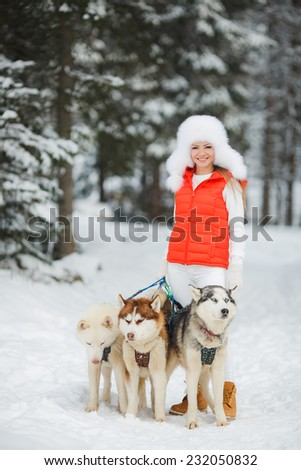 Happy young woman playing with siberian husky dogs in winter forest. Beautiful girl hugging the dog. The girl with the siberian husky