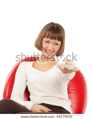 Happy young woman pointing remote control at TV