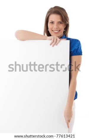 Happy young woman posing with blank sheet in studio, smiling at camera, copyspace.?