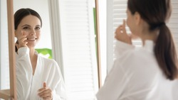 Happy young woman practicing skincare therapy procedures, applying moisturizing cosmetic lotion on face. Girl using cleaning facial cream to keep fresh healthy complexion. Mirror reflection.