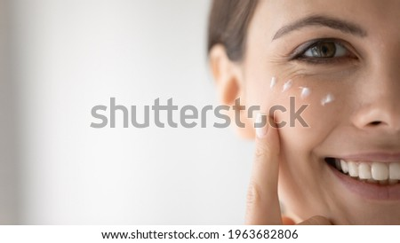 Happy young woman putting moisturizing nourishing cream, cleansing lotion on smiling face, applying cosmetics for keeping healthy fresh skin. Cosmetology, skincare concept, Close up, cropped portrait Stock photo ©