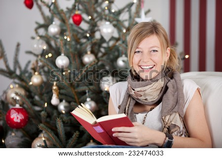 Happy young woman reading a book at Christmas as she sits in front of the Christmas tree looking at the camera with a lovely warm smile