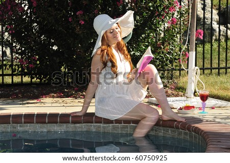 happy young woman reading a book by the pool