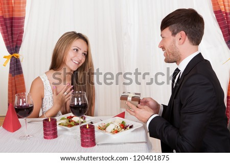 Happy young woman receives a gift from her partner. Romantic dinner setting with young couple dressed in evening wear
