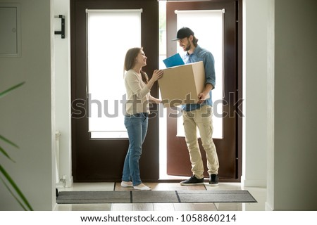 Happy young woman receiving parcel from smiling courier at home, delivery man holding carrying package giving cardboard box to customer receiver standing at doorway, door delivery service concept