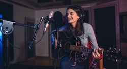 Happy young woman recording a song in a professional music studio. Smiling female sitting on front of microphone with guitar in recording studio.