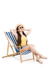 happy young woman resting on beach chair, isolated on white