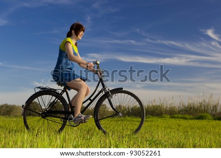 Happy young woman riding a bicycle in a beautiful green meadow