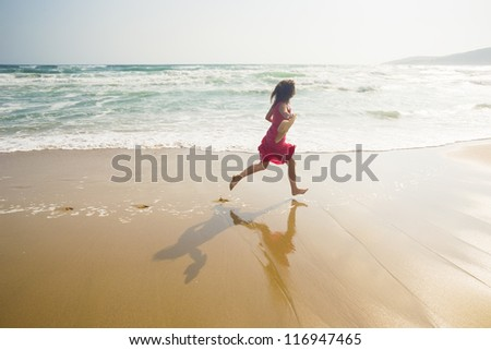 Happy young woman running along the beach