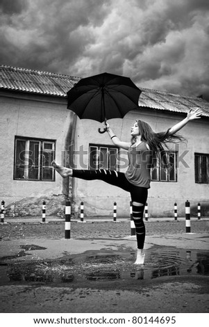 happy young woman running under rain