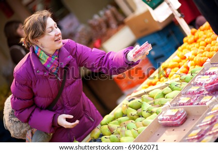 Happy young woman selecting fruits at fruit market