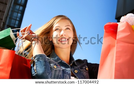 Happy young woman shopping and holding bags