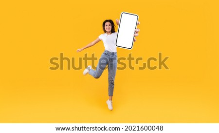 Happy young woman showing empty cellphone screen while jumping up on yellow studio background, collage, full body length, banner panorama. Excited lady recommending nice and useful mobile application