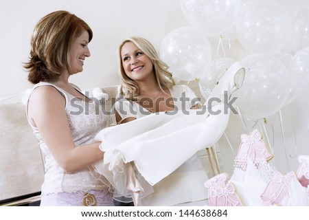 Happy young woman showing her dress to friend at the bridal shower