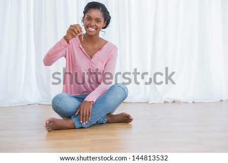 Happy young woman showing her new house keys and smiling at camera
