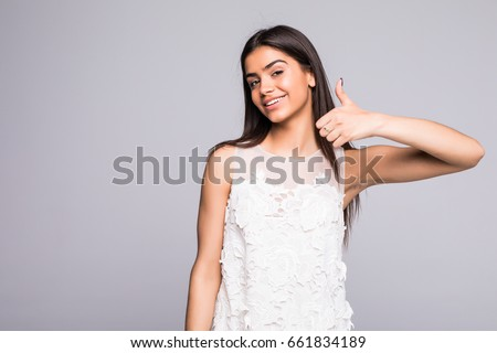 Happy young woman showing ok sign with fingers an winking isolated on a gray background