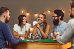 Happy young woman showing two aces while playing poker while sitting at a game table with her friends. Concept of themed celebrations of birthdays or corporate events in a casino or at home.