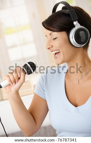 Happy young woman singing with microphone, listening music on headphones.?