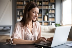 Happy young woman sit at desk look at laptop screen browsing surfing wireless Internet at home, smiling millennial female employee work on modern computer in living room, technology concept